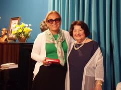 A poetisa e declamadora Gilda Baptista de Freitas faz a entrega de uma lembrança a Shirley Baesso