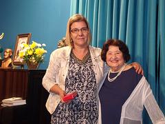 A poetisa e declamadora Gilda Baptista de Freitas faz a entrega de uma lembrança a Cátia Barros
