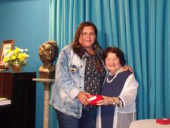 A poetisa e declamadora Gilda Baptista de Freitas faz a entrega de uma lembrança a Ana Claudia do Valle
