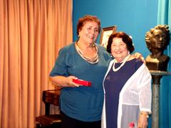 A poetisa e declamadora Gilda Baptista de Freitas faz a entrega de uma lembrança a Odette Diuana Saud