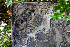 Detail of a churchyard monument now surrounded by holly, Twyford Church, Derbyshire