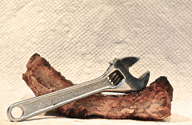 A Cresent Wrench Resting on a Bar-B-Qued Rib