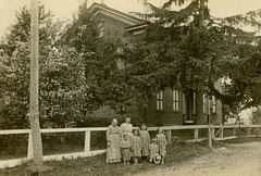Women and Kids in Front of a House