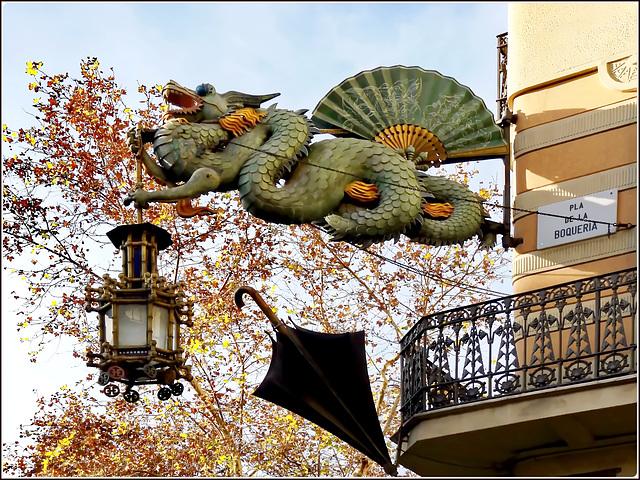 Barcellona : Pla de la Boqueria - Un drago sostiene il lampione sopra un antico negozio di ombrelli
