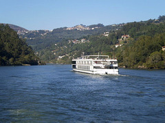 Cruise boat with cabins going downstream.