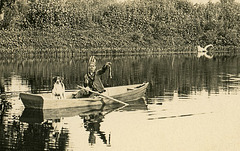 Playing Indian and Fishing with a Dog in a Rowboat (Cropped)