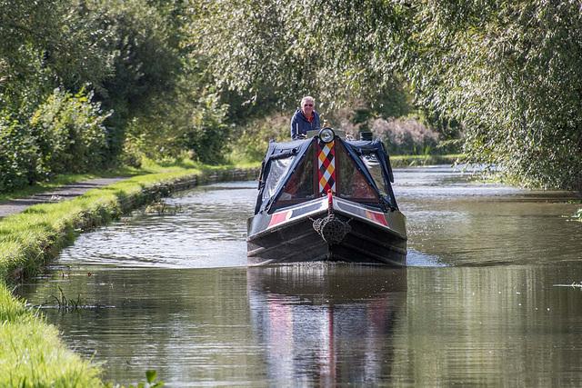 A narrow boat making slow progress long the canal