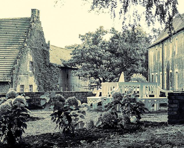 Neu angelegtes Sitzbankrondell (2016) mit Blick auf Scheune, Reitstall und Brauhaus (ca. 1650)