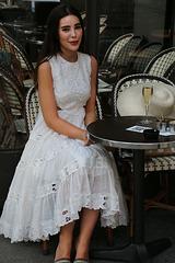 Dans un beau quartier de la capitale , jeune femme à la coupe de champagne et claquettes Christian Dior à 623 euros .