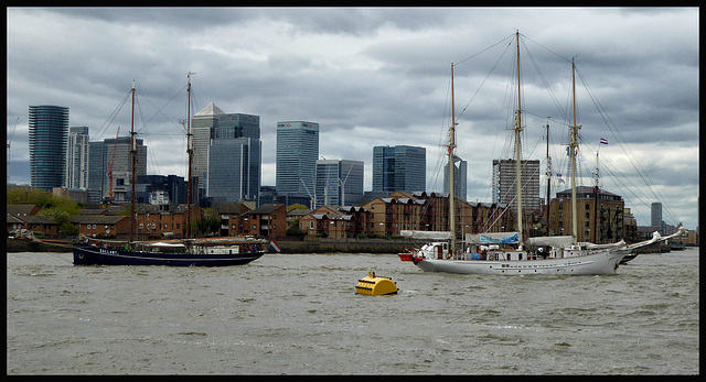 Two tall ships passing in front of Canary Wharf