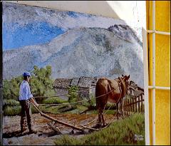 Oggetti appesi : un quadro campestre firmato appeso all'esterno di una casa del paese