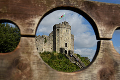 Cardiff Castle seen through medieval stocks.