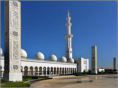 AbuDhabi : esterno del grande cortile al sole del mattino - un minareto ad angolo e tre obelischi delimitano l'area sul lato di levante