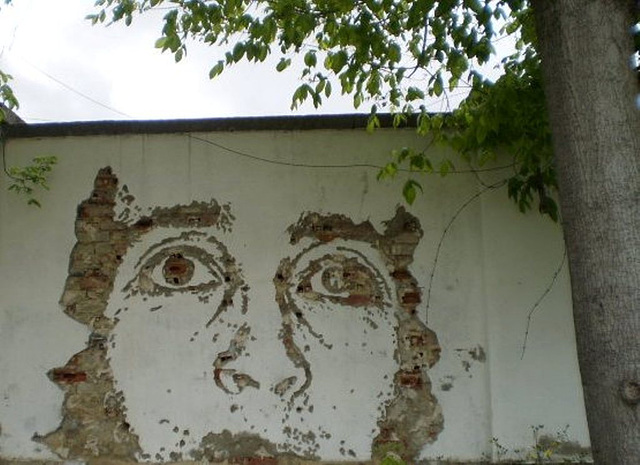 Vhils' mural on inside wall of ancient factory.