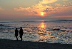 Spaziergang am Strand bei untergehender Sonne