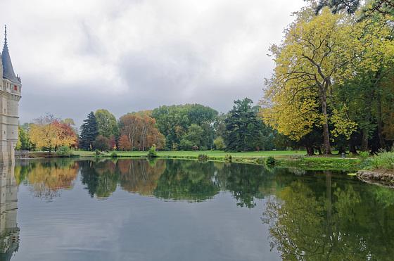 Bout de château, lac, parc avec arbres, nuages menaçants et quelques personnages dans le lointain