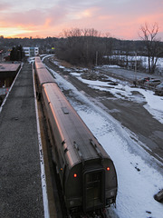 Watching an Amtrak from above as a sunset occurs.
