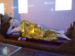 Buddha liegt gestützt von Kissen