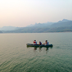 Paddling their canoe over Srinakarin lake in the morning in Kanchanaburi province, Thailand