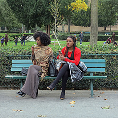 Two black girls sitting on the first bench on the right