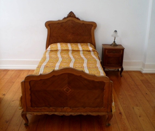 Single bed and bedside table of the poet Fernando Pessoa.