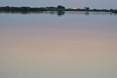 Impresigaj koloroj de la akvo dum la sunsubiro. Okavango-Delto