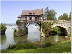 Quaint medieval millhouse hovers above the waters of the Seine