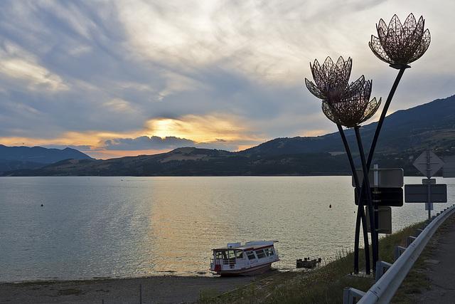 Le bateau au coucher du soleil (aux côtés de fleurs artistiques) sur le Lac de Serre-Ponçon, Savines-le-Lac, France