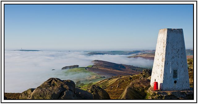 The Roaches trig point with fog below