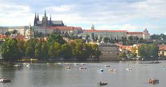 Praga Kastelo kaj la rivero Moldavo kun boatemuloj