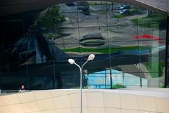 Ein Mann vor dem Spiegel der BMW Welt