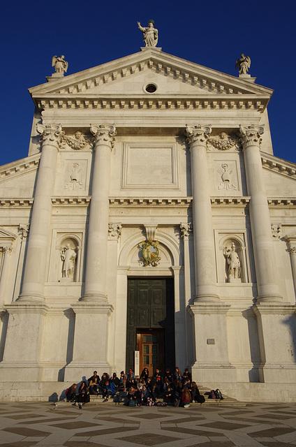 Students enjoying the sun in front of the Palladian facade of Chiesa di San Giorgio Maggiore