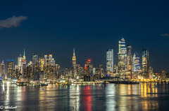 NYC cityscape lit up in colored lights along a waterfront