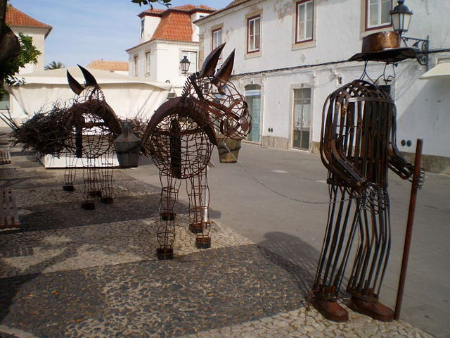 Sculpture of man leading donkeys.