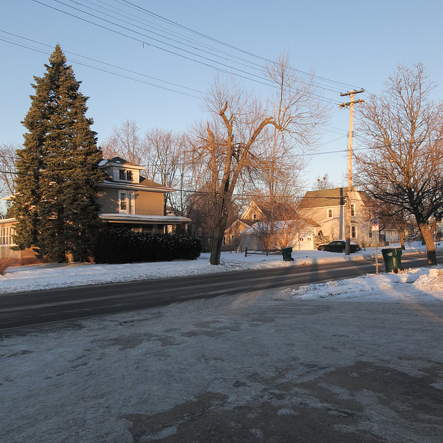 Winter evening residential scene with foreground of gas station driveway.