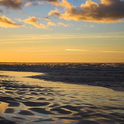 Der nasse Sand und die Wellen beim Sonnenuntergang
