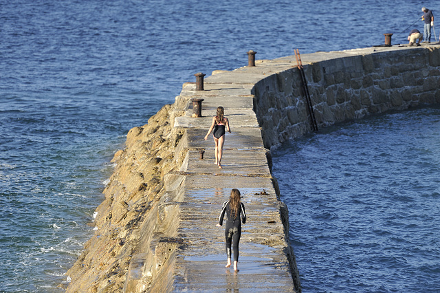 Girls running out to dive off the end of the sea wall. Sennen cove ~ Cornwall