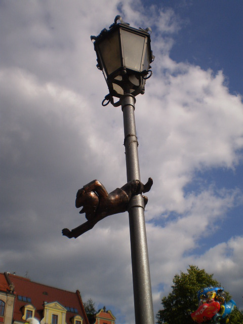 Bronze dwarf - acrobat on lamp pole.