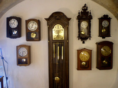 Standing clock and wall clocks.