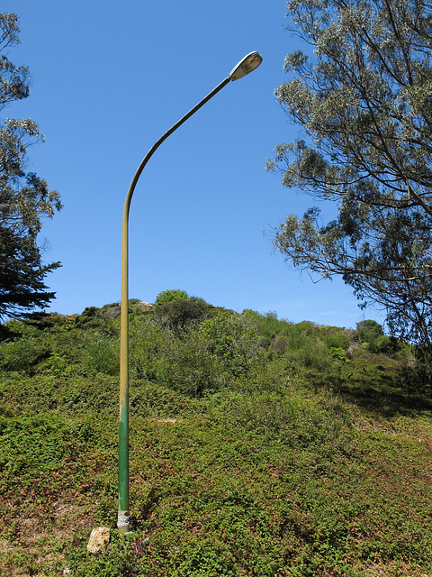 Lightpoles on hillsides in parklands in Australia and Greece.