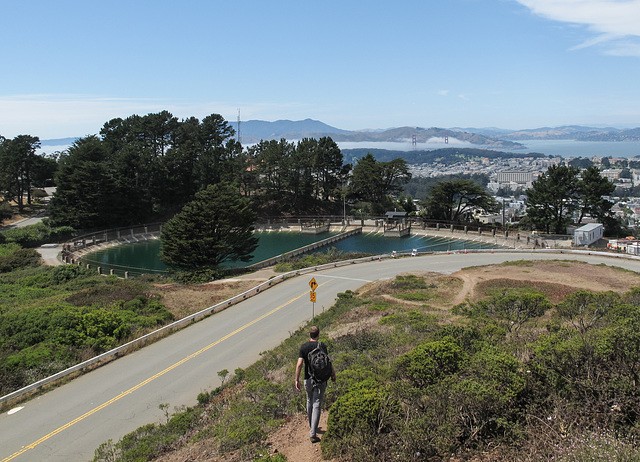 The Twin Peaks Reservoir; the faraway Golden Gate Bridge; and a young fella in descent.