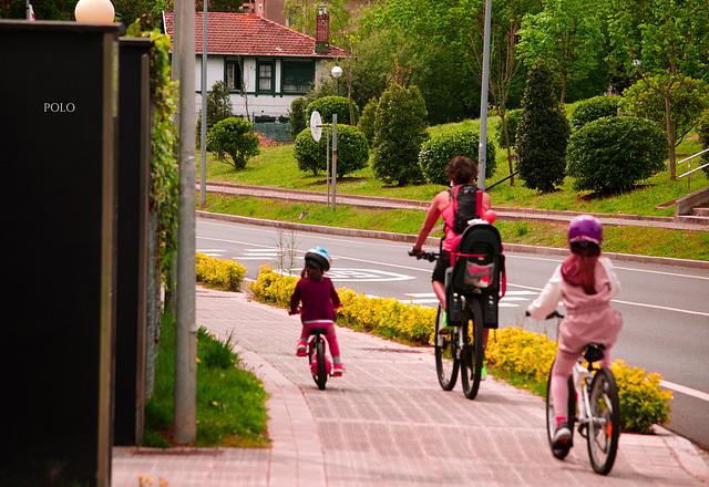 """Mamá y sus """"pollitos"""" en bicicleta."""