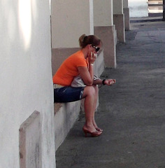 Cuban girl in high heels buzy with her cell phone