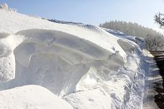 Schneewehen entlang einer schmalen Landstraße bei Vogt