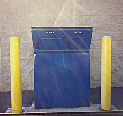 Blue box with yellow posts and fractured sunlight