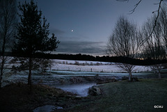 New moon over frosted fields at dusk
