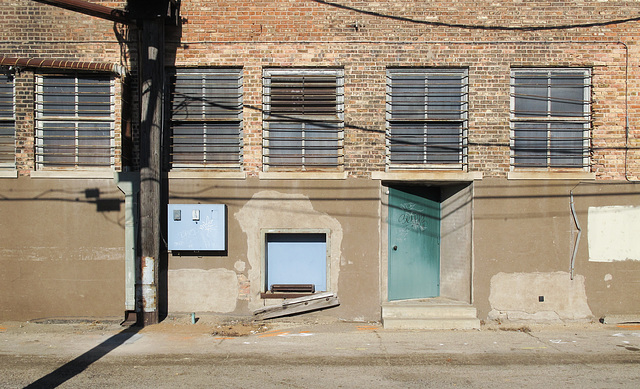 Good view of barred windows above a small loading dock and a diagonalized door.