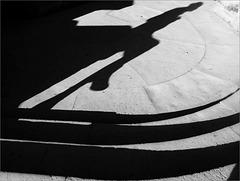 Jeu d'ombres avec femme assise sur un muret