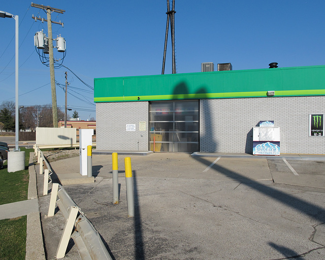 A bollards and guardrail scene of a McDonald's shadow cast upon a British Petroleum noncarwash with Monster drink and a badly leaning utility pole.