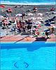 Sole e ombra sotto gli ombrelloni tra mare e piscina